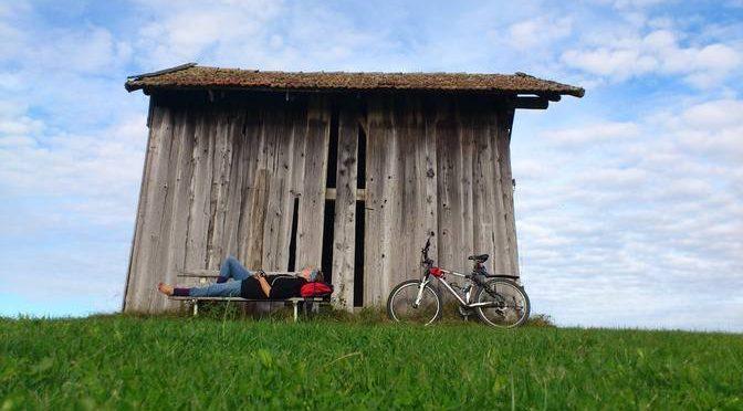 Eva liegt auf der Bank vor einer Hütte und neben ihr steht ihr Fahrrad