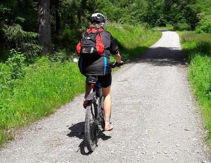 Eva fährt mit dem Mountainbike einen Forstweg entlang