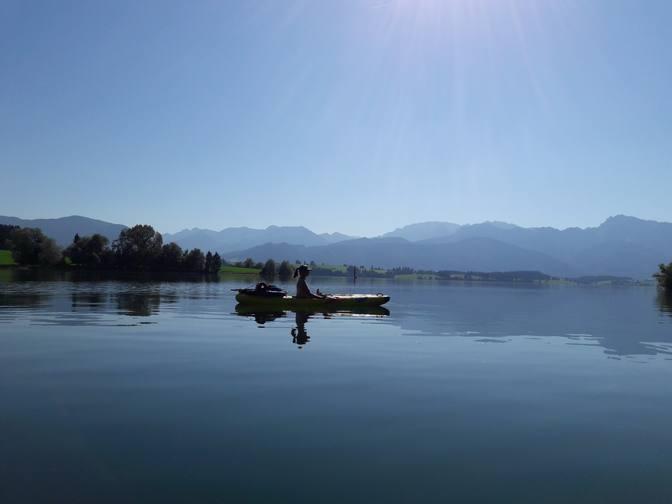 Eva paddelt im Kajak über den wundervollen Forggensee