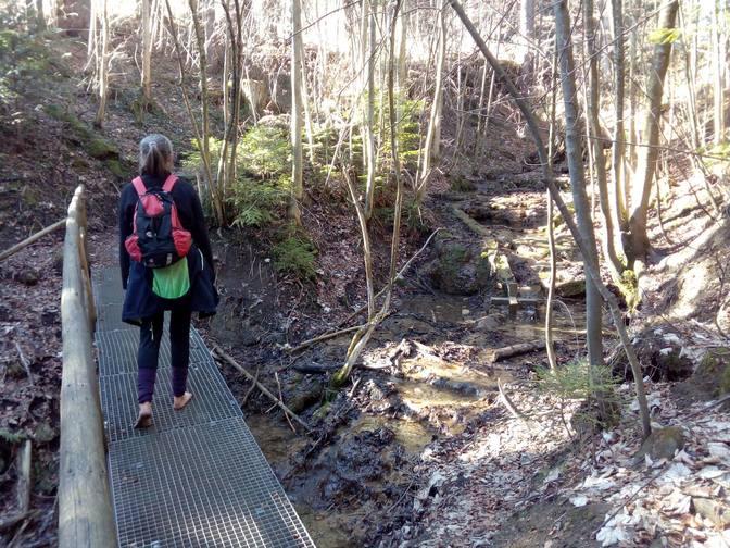 Eva läuft barfuß über eine Gitterbrücke
