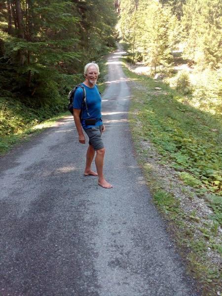 Wolfgang geht barfuß über die durchweg gesplittete Straße die zur Kappeler Alm führt