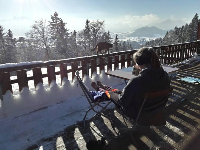 Eva sitzt im Winter draußen auf der Terrasse