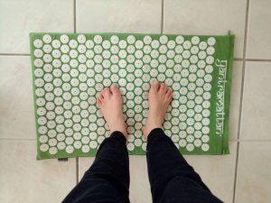 Trainieren der Fußsohlen mit Hilfe einer Akupressurmatte
