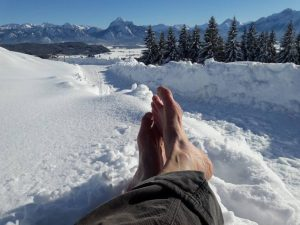 Barfuß im Schnee mit Bergsicht