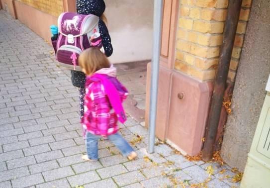 Kleines Mädchen läuft barfuß in der Stadt