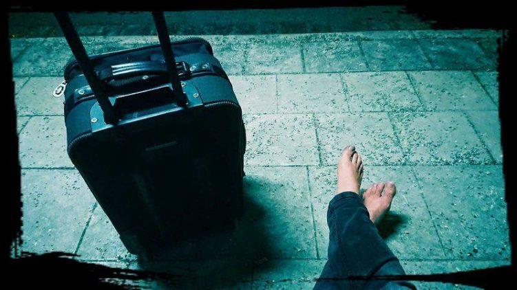 Barfuß neben einem Koffer