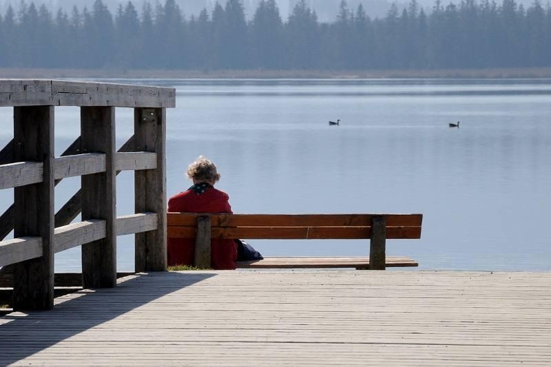 alte Frau auf Bank vor See