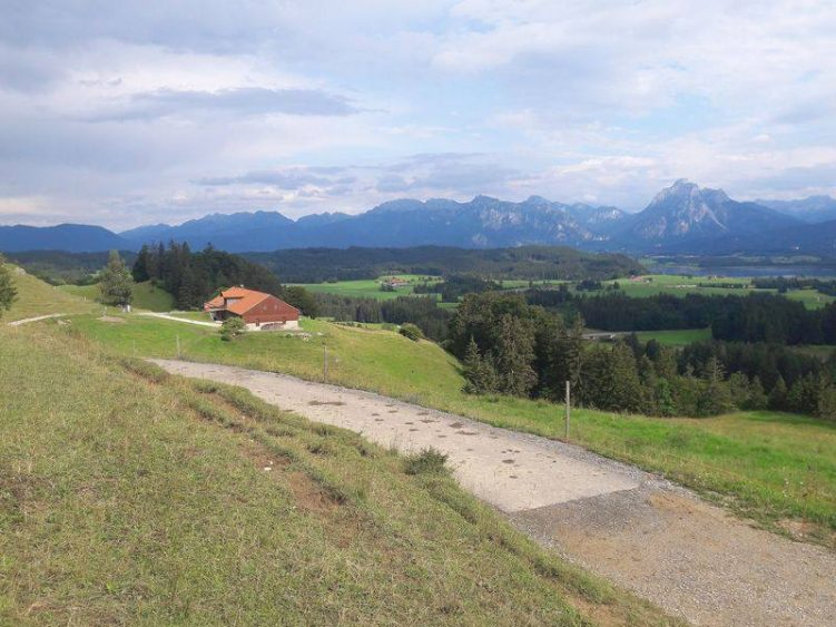 Ausblick auf die Hütte der Alpe, die Berge und einen Asphaltweg.