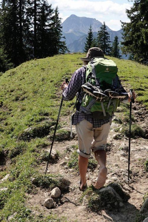 Eine ältere Dame geht barfuß über die Berge