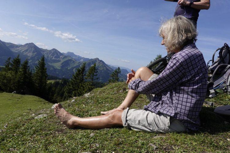 Eine ältere Dame sitzt barfuß am Gipfelkreuz des Schönkahler